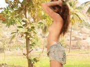 Девушка играет с голубыми стрингами под пальмой