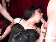 Женщина в корсете делает глубокий минет двум парням