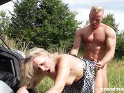 Зрелая баба у багажника машины впускает в норку крепкий член блондина