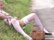 Блондинка присела на траву и, раздвинув ноги в чулках, устроила мастурбацию