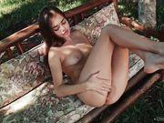 Девушка на природе вертит попкой и поглаживает руками бархатную кожу