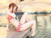 Рыженькая милашка в купальнике в горошек трогает киску возле бассейна