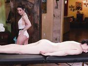 Девушка в кружевном белье массирует обнаженное тело брюнетки маслом