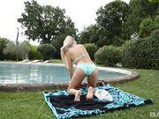 Красивая блондинка снимает купальник и наносит масло на загорелое тело
