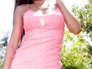 Красивая брюнетка эротично снимает кружевное платье и гладит киску в саду
